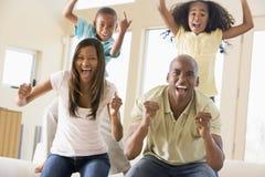 Familie in en woonkamer die toejuicht glimlacht Stock Foto's
