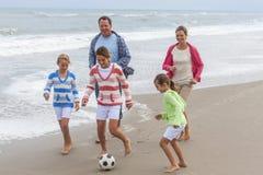 Familie erzieht die Kinder, die Strand-Fußball-Fußball spielen Stockfotografie
