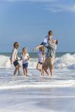 Familie erzieht die Mädchen-Kinder, die auf Strand spielen Stockfotografie