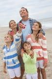 Familie erzieht die Mädchen-Kinder, die Drachen auf Strand fliegen Stockfotos
