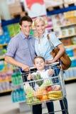 Familie fährt Einkaufslaufkatze mit dem Lebensmittel und kleinem Jungen, die dort sitzen Lizenzfreie Stockfotos