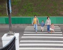 Familie gehen auf Überfahrtstraße Lizenzfreies Stockfoto