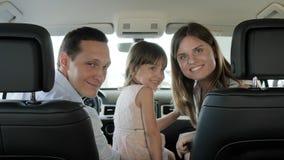 Familie geht auf Reise, Auto für das Reisen, Porträt von glücklichen Menschen im neuen Automobil, Touristeneltern und Kinder stock video footage