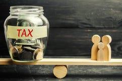 Familie, geld en de woorden` Belasting ` op de schalen Belastingen op onroerende goederen, betaling Sanctie, schuldvorderingen Re royalty-vrije stock foto