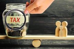 Familie, geld en de woorden` Belasting ` op de schalen Belastingen op onroerende goederen, betaling Sanctie, schuldvorderingen Re stock foto