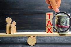 Familie, Geld und die Wörter 'Steuer 'auf den Skalen Steuern auf Immobilien, Zahlung Strafe, Rückstände Register von Steuerzahler stockfotografie