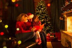 Familie gelezen verhalen bij de zitting van de Kerstmistijd op bank voor open haard stock afbeelding