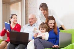 Familie genießt auf Sofa mit Laptops Stockfotos
