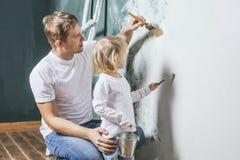 Familie, glückliche Tochter mit dem Vati, der Hauptreparatur tut, Farbenwände, Lizenzfreie Stockfotografie