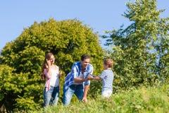 Familie in gras op weide royalty-vrije stock afbeelding