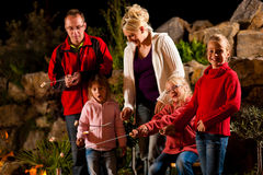 Familie am Grill am Abend lizenzfreie stockfotografie