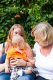 Familie - Großmutter, Mutter und Kind im Garten Stockfotos
