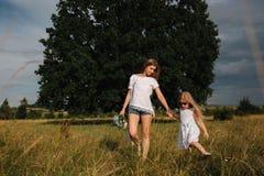 Familie haben Spaß außerhalb des nahen großen Baums Mutter- und Tochterweg zwar das Gras lizenzfreie stockfotos