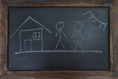 Familie, Haus und Sonne, malte Kreide auf einem schwarzen Brett Stockbild
