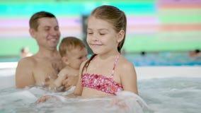 Familie het besteden tijd in een toevlucht` s Jacuzzi, die in borrelend water ontspannen stock video