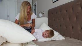 Familie het besteden vrije tijd thuis Vrolijke familie die pret met hun dochters op het bed hebben stock videobeelden