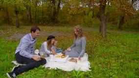 Familie in het de herfst Park en het eten van Frieten bij een picknick stock videobeelden