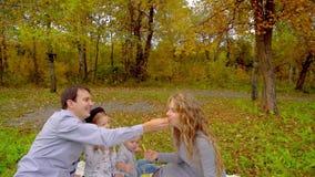 Familie in het de herfstpark die pret hebben die Frieten eten stock video