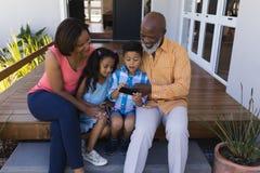 Familie het herzien foto de van meerdere generaties op mobiele telefoon op de portiek stock afbeelding