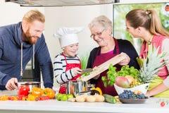 Familie het koken in multigenerationeel huishouden royalty-vrije stock afbeelding