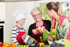 Familie het koken in multigenerationeel huishouden met zoon, moeder, royalty-vrije stock afbeelding
