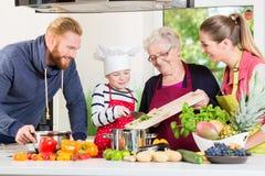 Familie het koken in multigenerationeel huishouden met zoon, moeder, royalty-vrije stock foto
