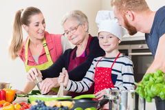 Familie het koken in multigenerationeel huishouden met zoon, moeder, stock fotografie