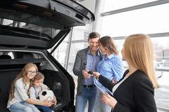 Familie het kopen auto in handel drijven, manager die autosleutels het geven stock afbeelding
