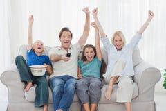 Familie het letten op televisie en het opheffen van wapens stock fotografie