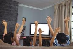 Familie het letten op televisie samen in woonkamer stock afbeelding