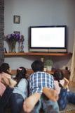 Familie het letten op televisie samen in woonkamer royalty-vrije stock afbeeldingen