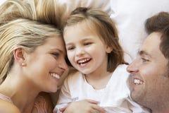 Familie het Ontspannen in Bed Stock Afbeeldingen