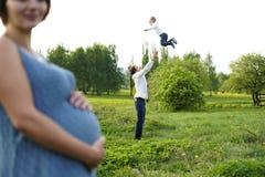 Familie Het portret van de familie Het jonge gelukkige familie openlucht lopen Zwanger vrouw, echtgenoot en Kind De papa werpt om royalty-vrije stock foto's