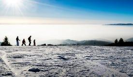 Familie het ski?en silhouetten bij piste Stock Fotografie