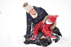 Familie het sledding in de winter op de sneeuw stock afbeeldingen