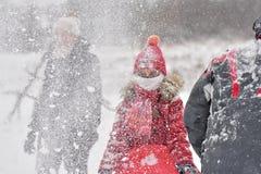 Familie het sledding in de winter op de sneeuw stock afbeelding