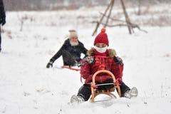 Familie het sledding in de winter op de sneeuw royalty-vrije stock fotografie