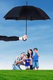 Familie het spelen bel bij gebied onder paraplu Stock Afbeeldingen