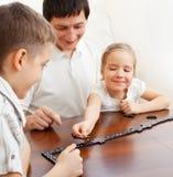 Familie het spelen domino's Stock Fotografie