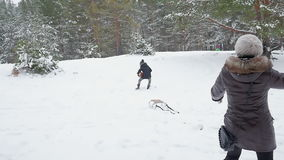 Familie het spelen door sneeuwballen in de winter 96fps te werpen stock footage