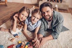 Familie het spelen met aannemer en thuis het liggen op vloer royalty-vrije stock fotografie