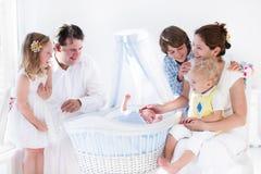 Familie het spelen met pasgeboren kind in witte mandewieg royalty-vrije stock fotografie