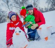 Familie het spelen sneeuw stock foto's