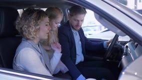 Familie im Auto-Vertragshändler, im glücklichen Ehemann und in der Frau mit dem Kind, das neues Automobil beim Sitzen in der Kabi stock footage