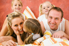 Familie im Bett â wenig Kuss Stockfotos