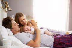 Familie im Bett, das schlafende neugeborene Baby-Tochter hält Stockfotografie