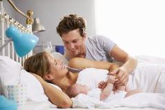 Familie im Bett, das schlafende neugeborene Baby-Tochter hält Stockbild