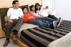 Familie im Bettblickfernsehen Lizenzfreie Stockbilder