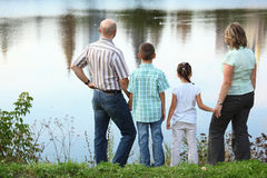 Familie im frühen Fallpark nahe Teich lizenzfreie stockbilder