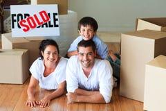 Familie im neuen Haus, das auf Fußboden mit Kästen liegt Stockfoto